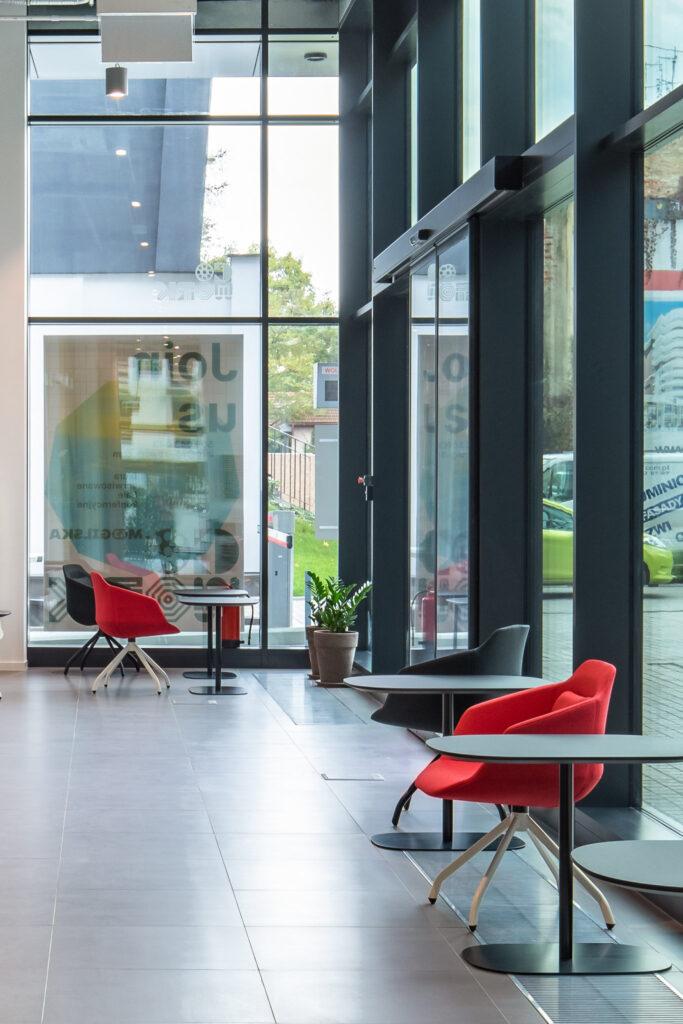 Fotografia przestrzeni coworkingowej z czerwonymi i czarnymi krzesłami w Warszawie