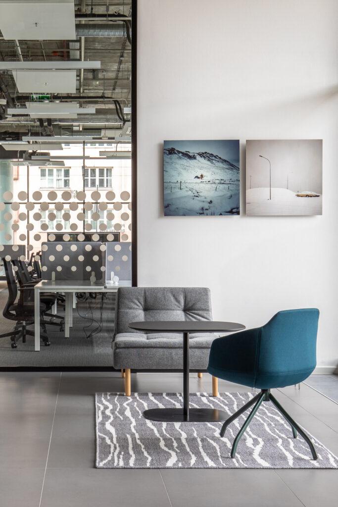 Fotografia przestrzeni biurowej z szarym fotelem i niebieskim krzesłem