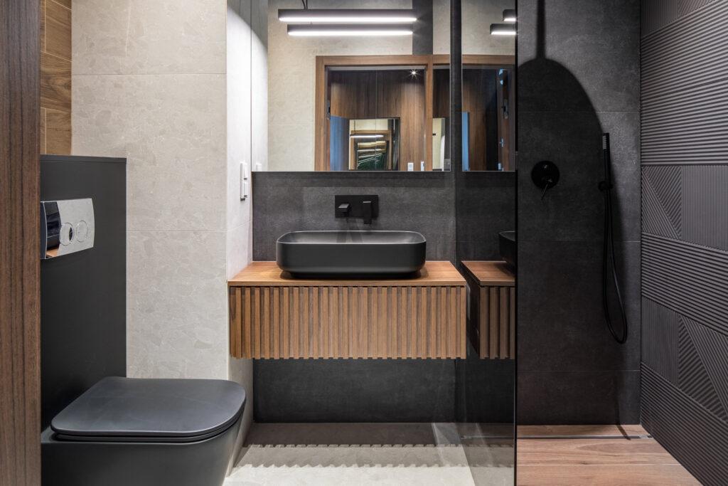 Fotografia wnętrza łazienki z grafitowymi płytkami i drewnianymi dodatkami