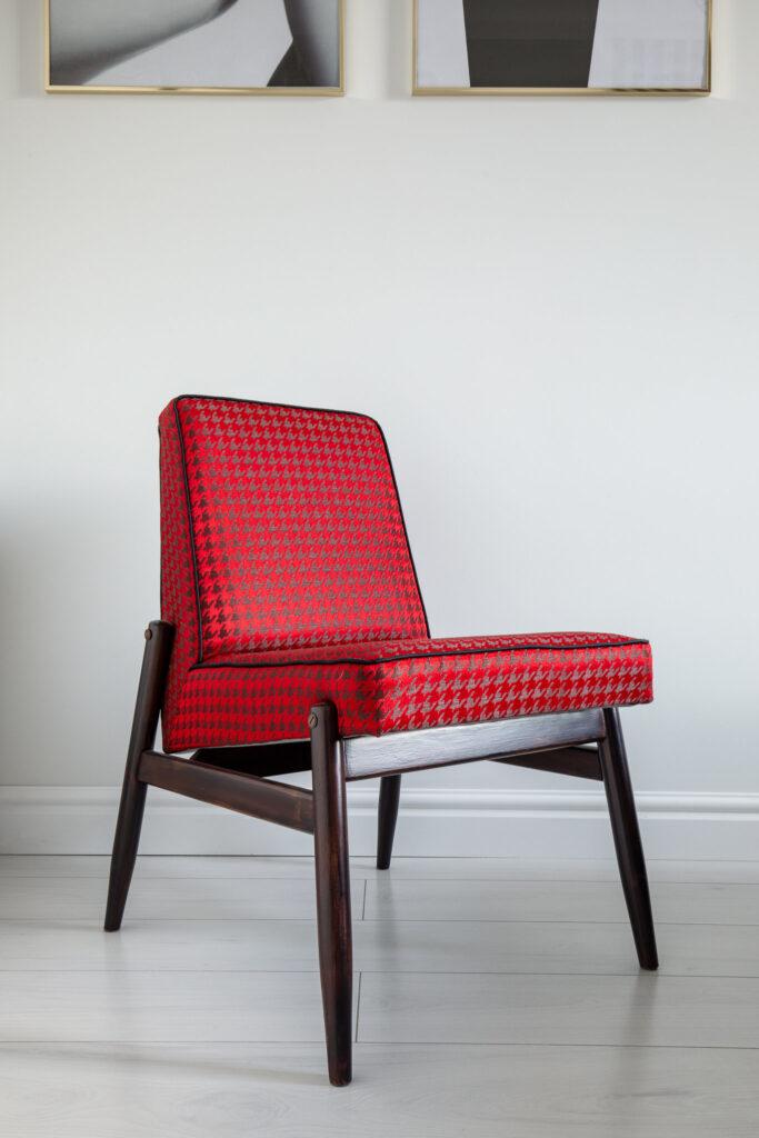 Fotografia krzesła z czerwonym obiciem i drewnianymi nogami