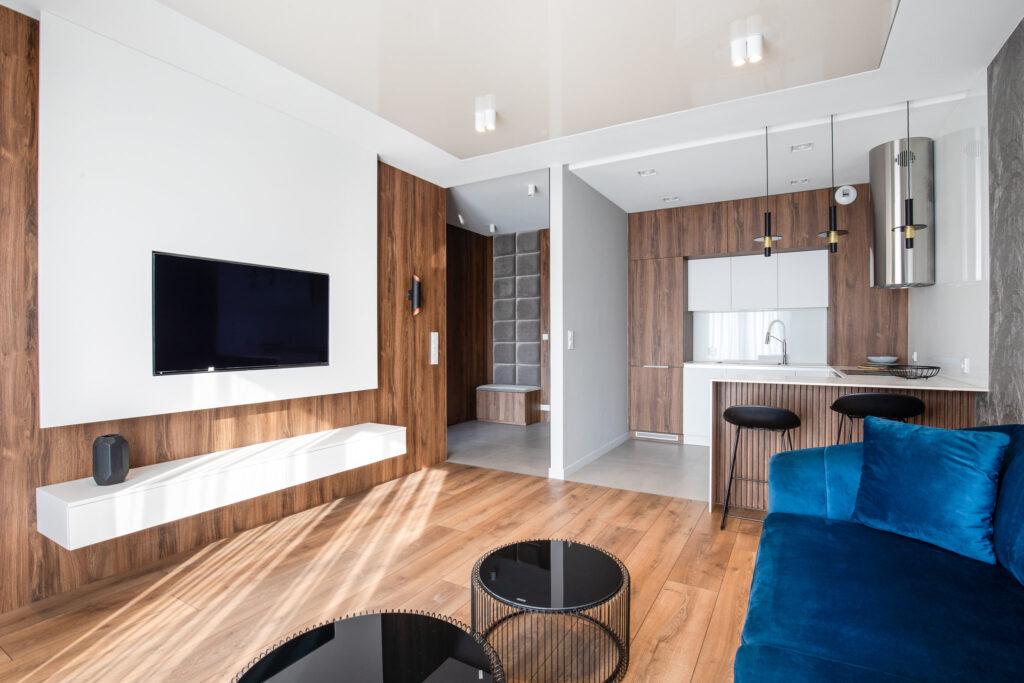 Fotografia wnętrza salonu z granatową sofą i drewnianym aneksem kuchennym