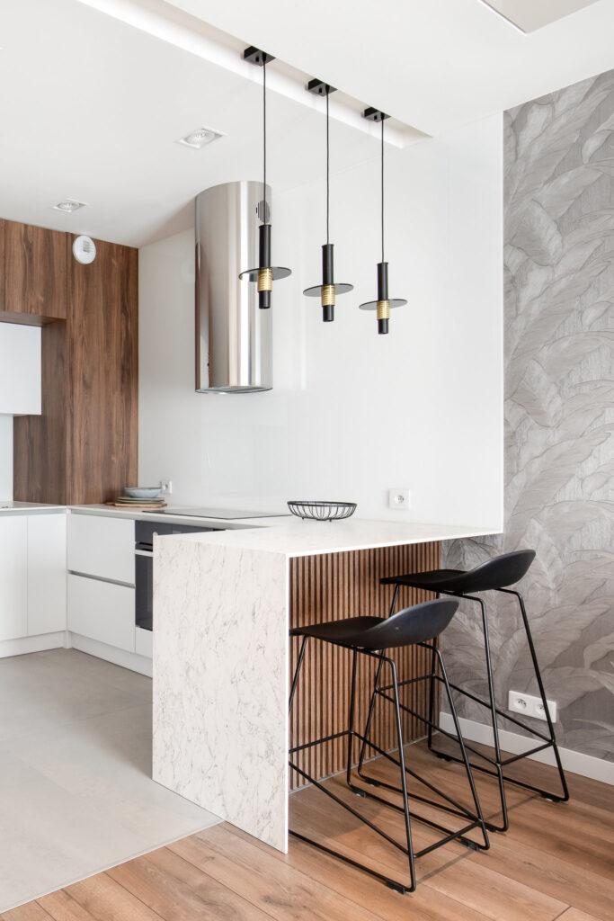 Fotografia kuchni wraz z wyspą kuchenną oraz z czarnymi barowymi krzesłami