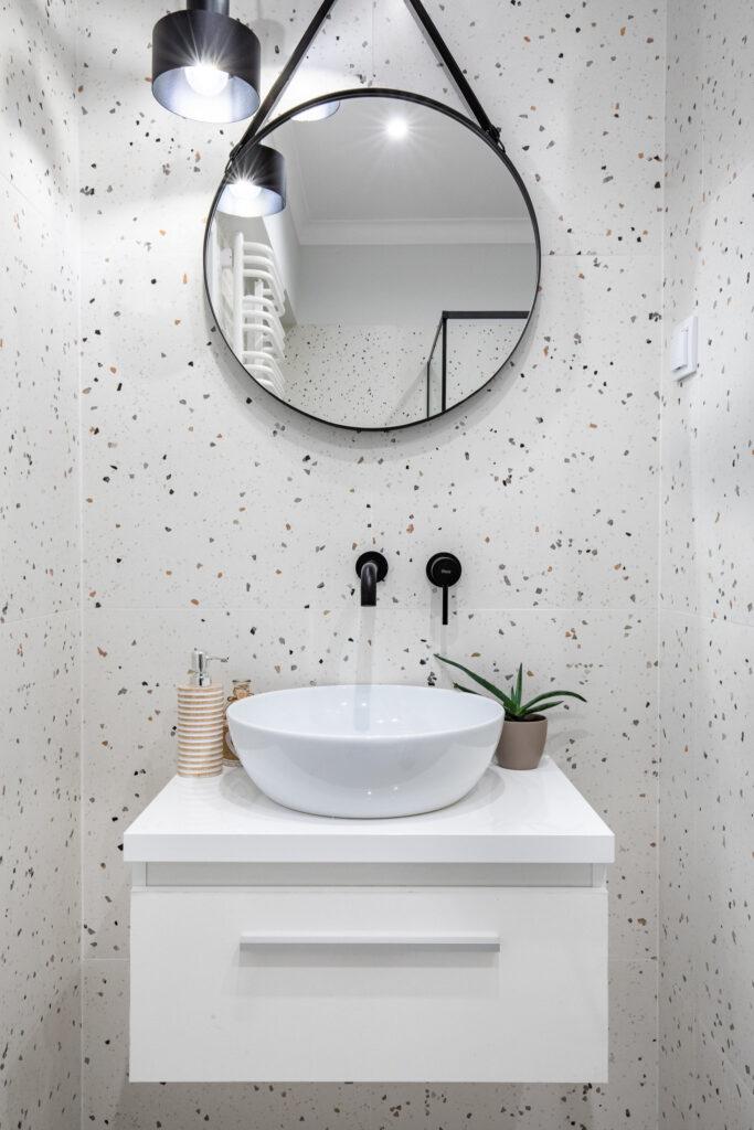 Fotografia wnętrza łazienki z białą szafką, umywalką oraz czarnym kranem