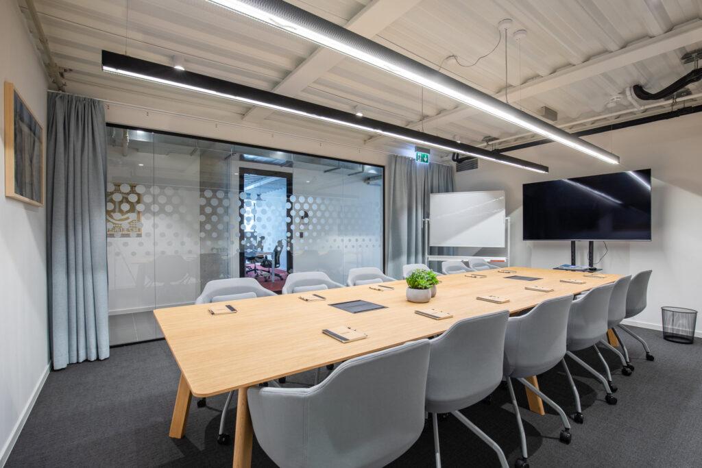 Fotografia przestrzeni sali biurowej ze stołem, szarymi krzesłami oraz telewizorem