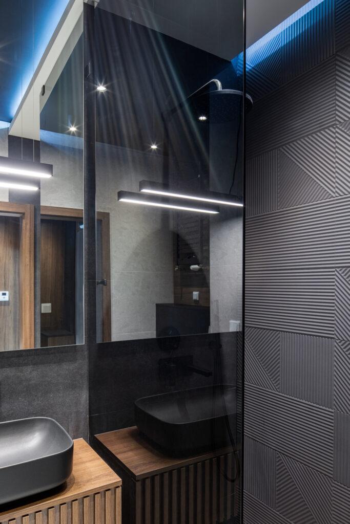 Fotografia łazienki z czarnym prysznicem i grafitowymi płytkami