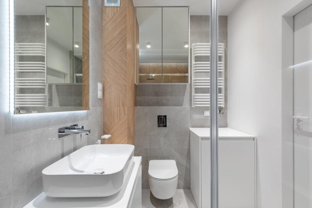 Fotografia jasnej szaro-białej łazienki z toaletą oraz szafka z lustrem