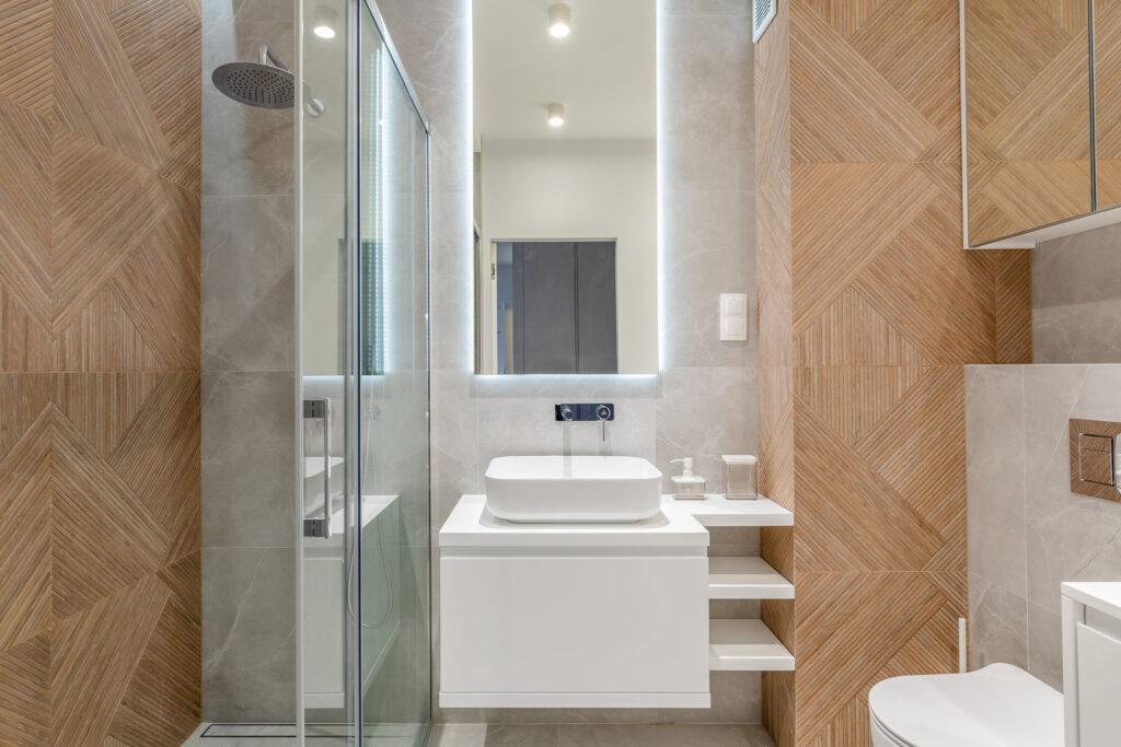 Fotografia wnętrza łazienki w aranżacji z jasnego drewna z karmelowymi płytkami