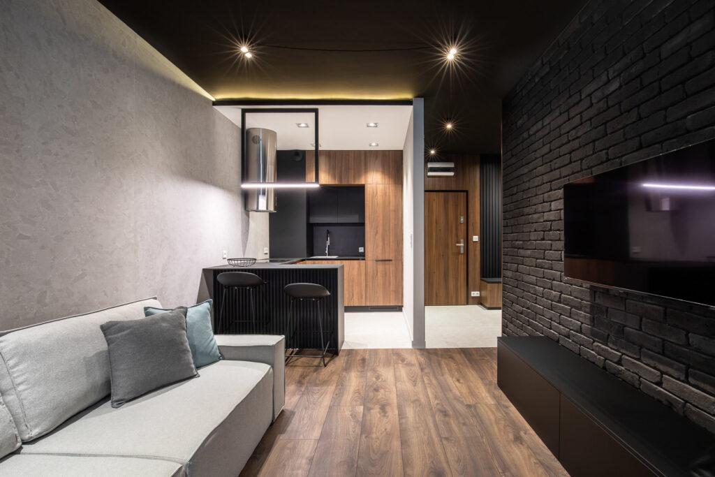 Fotografia salonu z szara sofa i czarna cegłą na ścianie w mieszkaniu na ul Rakowickiej w Krakowie