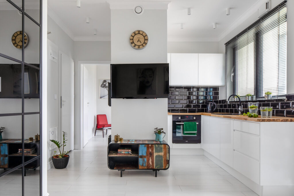 Fotografia kuchni z kącikiem telewizyjnym i wejściem do sypialni