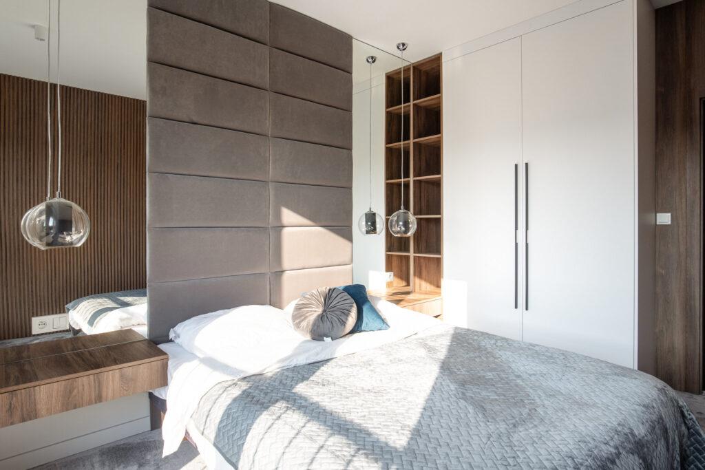 Fotografia wnętrza sypialni z drewnianym łóżkiem i wiszącymi okrągłymi lampami